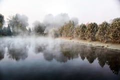 Mystisk dimma över sjön i morgonen Arkivbild
