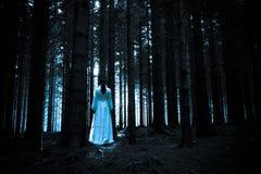 Mystisk flicka i mörk spöklik skog Arkivfoto