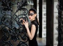 Mystisk kvinna i den venetian karnevalmaskeringen nära smidesjärnporten Arkivfoto