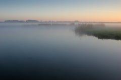 Mystisk sjö med morgondimma Arkivfoto
