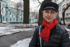 Mystisk smyle av den stilfulla medelåldersa kvinnan i röd halsduk och b royaltyfria foton