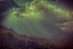 Mystiskt bergs landskap för by med dimma Royaltyfri Bild