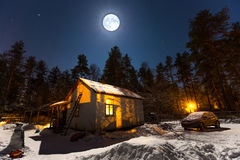 Mystiskt byhus som täckas med insnöat månsken arkivfoton