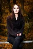 Mystiskt kvinnasammanträde på en bänk i skogen Arkivfoto