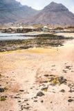Mystiskt landskap av den sandiga kustlinjen med fisherbyn och svarta vulkaniska berg i bakgrund Baia Das Gatas arkivbilder