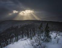 Mystiskt solljus som häller till och med en mörk berghimmel i Catskillsen arkivbild