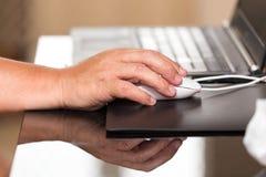 Mysz w ręce przy pracą na laptopie Obrazy Royalty Free