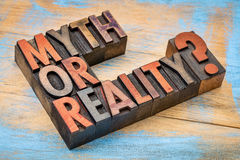Myth or reality? QUestion in wood type. Myth or reality?A question in vintage letterpress wood type against grunge painted wood Royalty Free Stock Photos