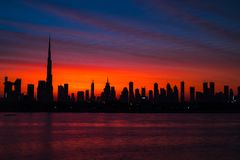 Mythical bloody red sky over Dubai. Dawn, morning, sunrise or dusk over Burj Khalifa. Beautiful colored cloudy sky over. Dubai downtown . Glow over buildings or stock images