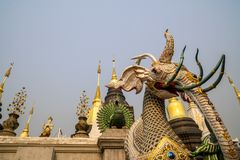 A mythical creature with elephant-like head in front of group of pagodas in a Buddhist temple in Thailand. stock image