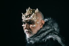 Mythical king of permafrost realm in fur collar isolated on black background. Magical beast with golden reptile skin and. Sharp thorns on face, fantasy and stock photography