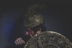 Mythologie, bärtiger Mannkrieger mit Metallsturzhelm und Schild, wird es tun Stockfotos
