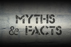 Myths and facts gr. Myths and facts stencil print on the grunge white brick wall Stock Photo