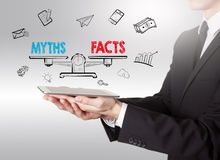 Myths vs facts Balance, young man holding a tablet computer.  Royalty Free Stock Photography