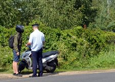 The inspector of the road police patrol checks the documents from the driver of the motorbike. MYTISHCHI, RUSSIA - AUGUST 12, 2017:The inspector of the road Royalty Free Stock Photos