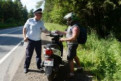 The inspector of the road police patrol checks the documents from the driver of the motorbike. MYTISHCHI, RUSSIA - AUGUST 12, 2017:The inspector of the road Royalty Free Stock Images