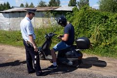 The inspector of the road police patrol checks the documents from the driver of the motorbike. MYTISHCHI, RUSSIA - AUGUST 12, 2017:The inspector of the road Royalty Free Stock Photo