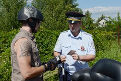 The inspector of the road police patrol checks the documents from the driver of the motorcycle. MYTISHCHI, RUSSIA - AUGUST 12, 2017: The inspector of the road Stock Images