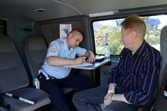An inspector of the road police patrol service makes a report on the violation of traffic rules. MYTISHCHI, RUSSIA - AUGUST 12, 2017: An inspector of the road Royalty Free Stock Photography