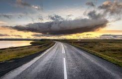 Myvatn, Ισλανδία - δραματικό σύννεφο επάνω από τον κενό δρόμο στο ηλιοβασίλεμα Στοκ Φωτογραφία