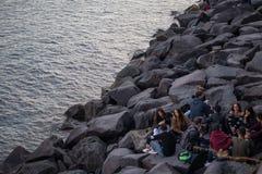 NÁPOLES, ITALIA - 4 de noviembre de 2018 La orilla del mar de Napoli gente de reclinación en las rocas Puesta del sol fotos de archivo