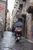 NÁPOLES, ITALIA - 4 de noviembre de 2018 Moto del montar a caballo del hombre joven debajo del paraguas bajo la lluvia imagenes de archivo