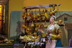 Nápoles, San Gregorio Armeno, representación en el pesebre napolitano de un banquete del queso con un vendedor en el primero plan imagenes de archivo