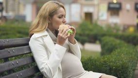 Náusea de sentimento fêmea grávida ao morder o hamburguer, toxemia da manhã, saúde vídeos de arquivo
