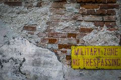Não cruze a placa vermelha em um fundo amarelo que pendura em uma parede de tijolo quebrada Fotografia de Stock Royalty Free