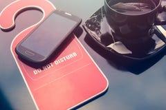 Não fazem o sinal do disturbe, um copo do chá e um telefone celular sobre o fundo escuro Hora para o conceito do resto Fotografia de Stock Royalty Free