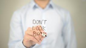 Não olhe para trás, escrita do homem na tela transparente imagem de stock