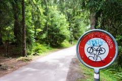 Não passe o sinal da parada para bicicletas na floresta com etiquetas dos grafittis Foto de Stock Royalty Free