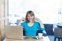 Não queira ouvir-se! O retrato do freelancer interessante atrativo da moça na blusa azul está sentando-se no café e está fazendo- imagens de stock