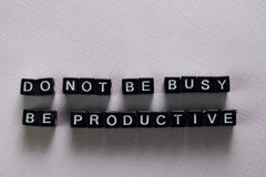 Não seja ocupado, seja produtivo em blocos de madeira Conceito da motiva??o e da inspira??o imagens de stock royalty free