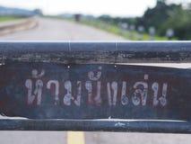 Não sente aqui o sinal cinzento, sinal da língua tailandesa com fundo da estrada Imagem de Stock Royalty Free