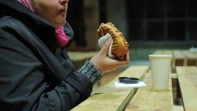 nächstenliebe Arme hungrige pralle Frau, die Würstchen isst Ungesundes Lebensmittel, überladen stock footage