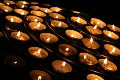 Nächstenliebe. Betende Kerzen in einem Tempel. Stockfotografie
