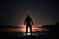 Nächtlicher Himmel über See mit dem Schattenbild des Mannes Stockfotos