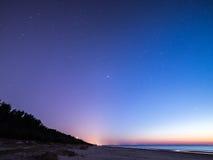 Nächtlicher Himmel mit Sternen auf dem Strand Auftragsnummer von Bereichen am Horizont des bedeutenden blauen Planeten Lizenzfreie Stockfotos