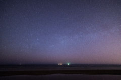 Nächtlicher Himmel mit Sternen auf dem Strand Auftragsnummer von Bereichen am Horizont des bedeutenden blauen Planeten Lizenzfreie Stockbilder