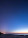 Nächtlicher Himmel mit Sternen auf dem Strand Auftragsnummer von Bereichen am Horizont des bedeutenden blauen Planeten Stockfotografie