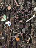 Nägel und Heftklammern und gelegentliche Stückchen des Materials verschickt in einen Laternenpfahl stockbild
