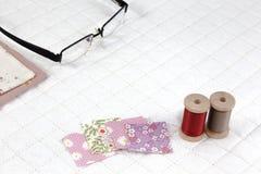 Näharbeit gesetzt auf weißen Patchwork Steppdeckenhintergrund Lizenzfreie Stockfotos