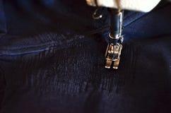 Nähen, Stich ein Loch in den dunklen Jeans oder sweatpants mit einer Nähmaschine stricken Teil der Nähmaschine- und Denimnahaufna stockfoto
