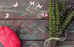 Nähen und Stricken Stricken auf einem hölzernen Hintergrund Knöpfe in Form von Herzen und Schmetterlingen Lizenzfreie Stockbilder