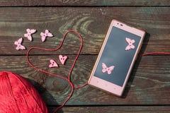 Nähen und Stricken Stricken auf einem hölzernen Hintergrund Knöpfe in Form von Herzen und Schmetterlingen Lizenzfreie Stockfotos