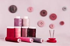 Nähende Ausrüstung mit Knöpfen auf rosa Hintergrund Stockbild