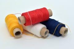 Nähende farbige Faden: gelb, rot, dunkelblau, weiß stockbild