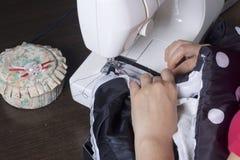 Nähende Kleidung durch einen einzelnen Unternehmer Eine Frau arbeitet an einer Nähmaschine Staples die Schnittelemente des Produk Lizenzfreies Stockbild
