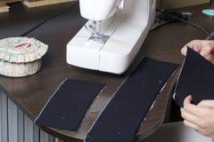 Nähende Kleidung durch einen einzelnen Unternehmer Eine Frau arbeitet an einer Nähmaschine Staples die Schnittelemente des Produk Lizenzfreie Stockfotos